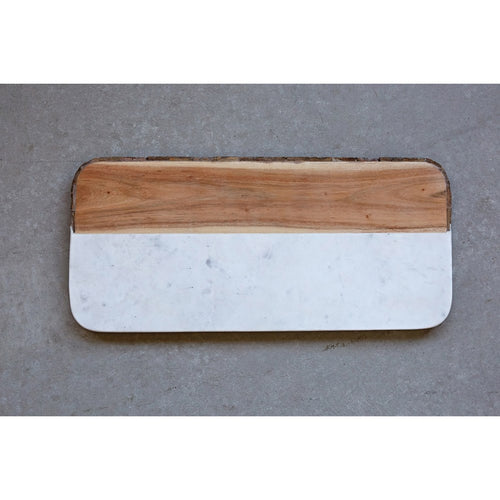 Wood and marble cutting board featuring a bark edge where the wood is. Cutting board is rectangle shaped with curved edges and is a little over half marble. Marble slab meets light wood horizontally with a real bark edge.
