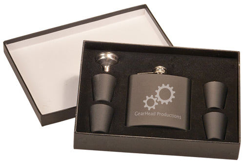Matte black flask and four matte black shot glasses with a shiny silver small funnel. The flask is engraved with a silver company logo. The flask, shot glasses, and funnel are displayed in foam inside a rectangle shaped gift box with a lid.