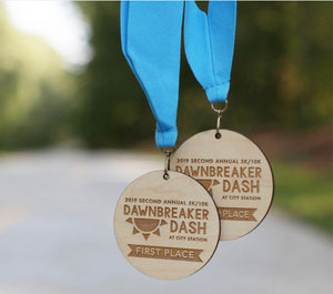 Large wood burned wooden medallions with light blue neck ribbons.