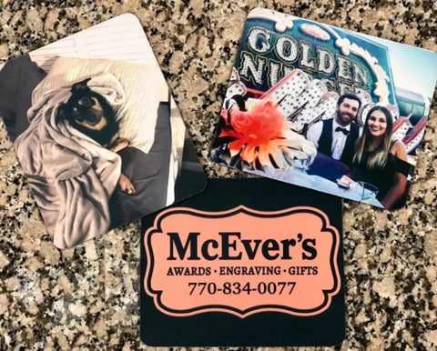 Three mouse pads engraved with photos. One mouse pad features a photo of a dog, another is engraved with a black and bronze company logo, and one is engraved with a photo of a man and woman at a wedding.