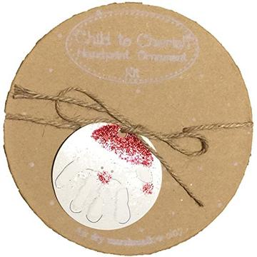 Brown cardboard circle box with twine that contains a clay baby hand print ornament kit.