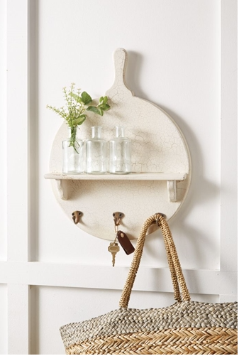 Large paddle shaped white rustic wall decor featuring a name cut out at the top and a shelf in the middle holding three small jars with greenery.  Underneath the shelf are three hooks holding a key and a bag.