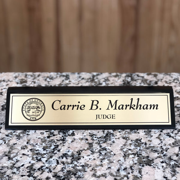 Black and gold personalized desk name plate.