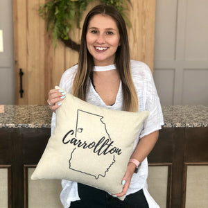 "Tan canvas material pillow engraved with the outline of the state of Georgia and the city name ""Carrollton"" through the middle in a a black cursive font."
