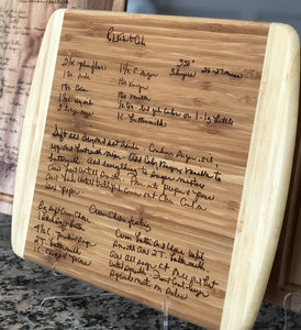Large rectangle shaped light wood cutting board featuring two curved ends that are a lighter wood than the center. The center of the cutting board is engraved with a hand written recipe wood burned into the cutting board.