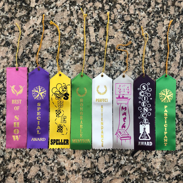 Eight different lapel ribbons all with different themes are displayed. Best of show, special award, spelling award, perfect attendance, math award, science award, and participation award.