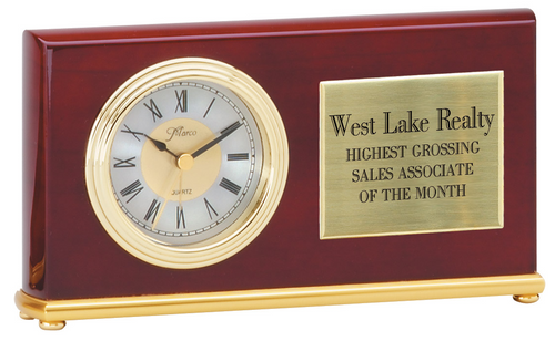 High gloss rosewood horizontal clock with brushed gold feet. There is a white clock face with black hands and roman numerals on the left side of the clock. The right side of the clock houses a gold engraved plate that matches the gold hardware of the clock.