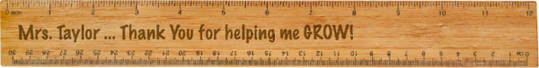 "Wood burned wooden ruler that reads ""Mrs Taylor... Thank You for helping me GROW!"" in the center."