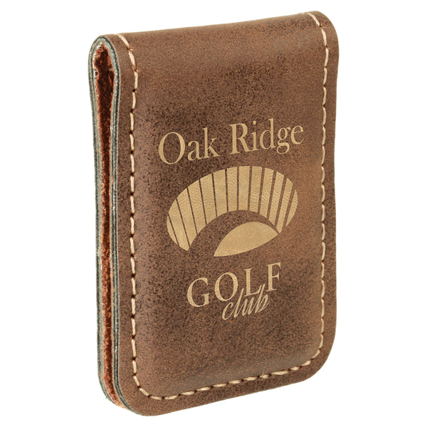 Brown rustic rectangular shaped magnetic money clip. The front of the money clip is engraved with a gold company logo.