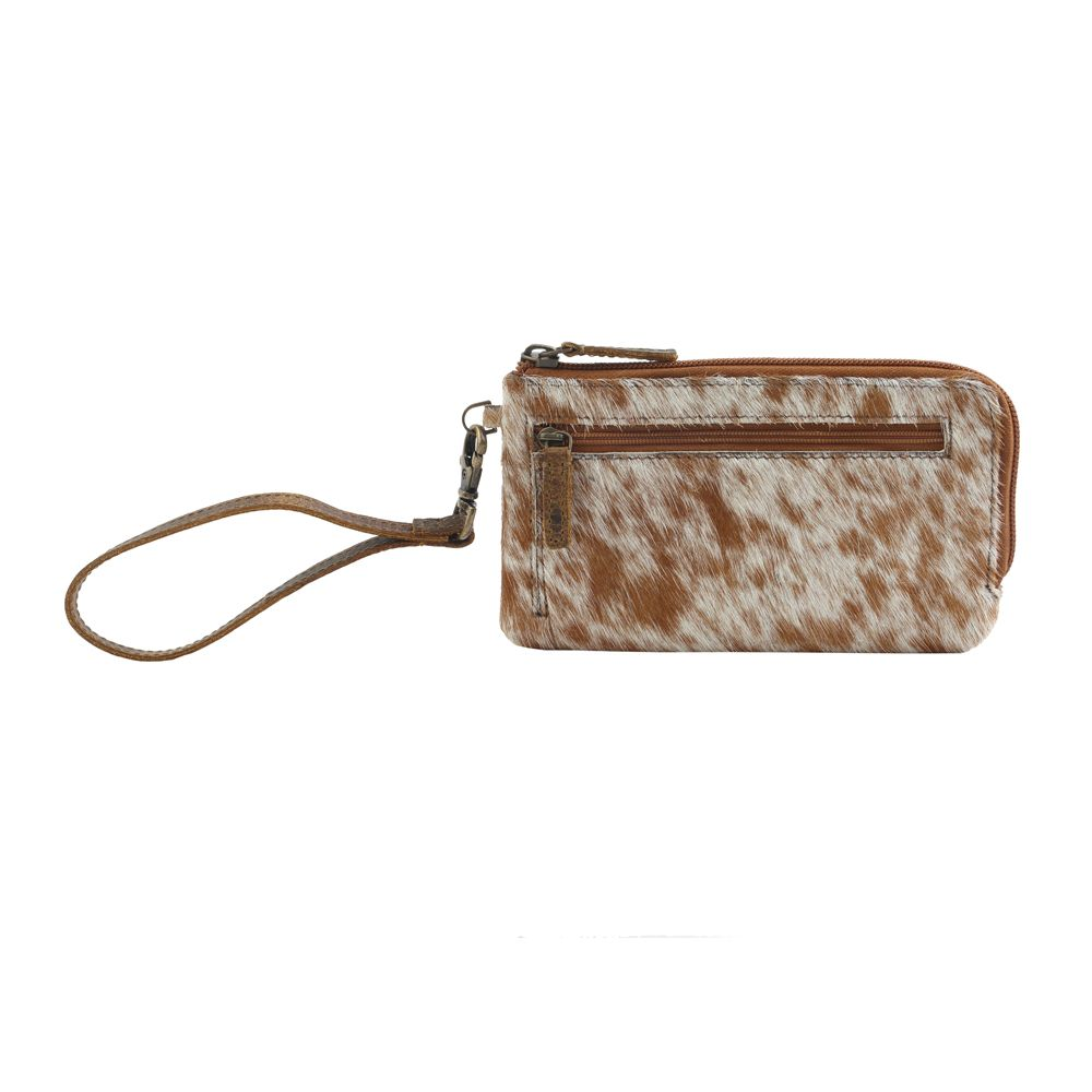 white and brown cowhide wristlet
