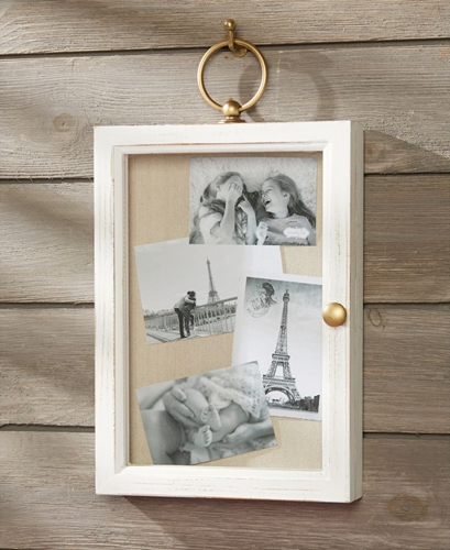 White shadow box with a gold ring to be hung on the wall and a gold pull to open the box. The front of the shadow box is glass and features a tan canvas inside with black and white photos displayed.