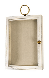 White shadow box with a gold ring to be hung on the wall and a gold pull to open the box. The front of the shadow box is glass and features a tan canvas inside.