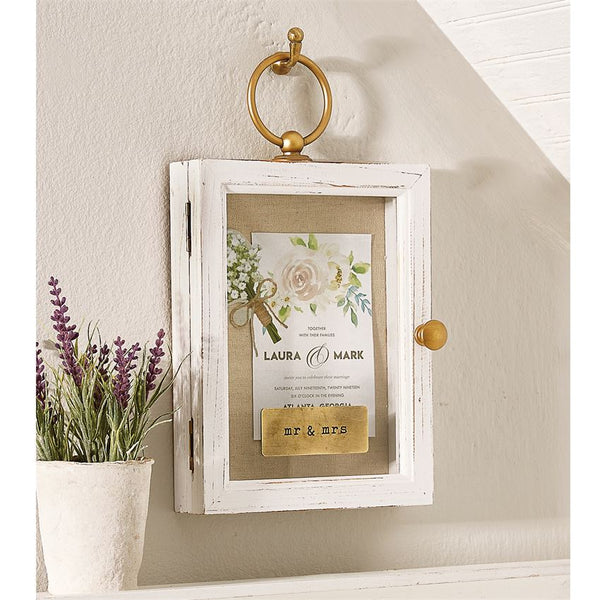 White shadow box with a gold ring to be hung on the wall and a gold pull to open the box. The front of the shadow box is glass and features a tan canvas inside with wedding keepsakes displayed.