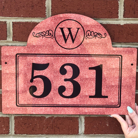"Rust colored rectangle mail box sign engrav ed with large black numbers in the center. The top of the sign is a semi circle shape and features a ""W"" with a circle and scroll design."