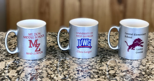 Three silver sparkle glass coffee mugs each engraved with a different school logo and name.