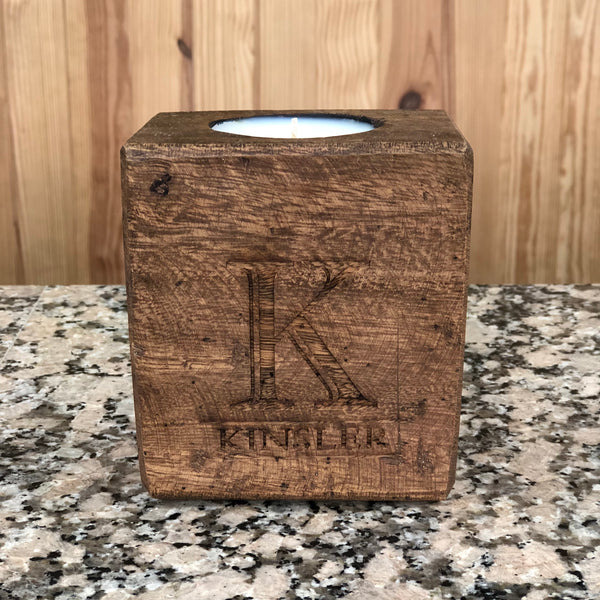 Wooden sugar mold candle that is wood burned with a last name on the front.