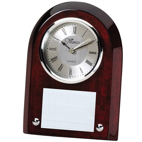 Small high gloss rosewood clock with a curved top and beveled edges. Features a silver face with black roman numerals and  an engraved plate below the face.