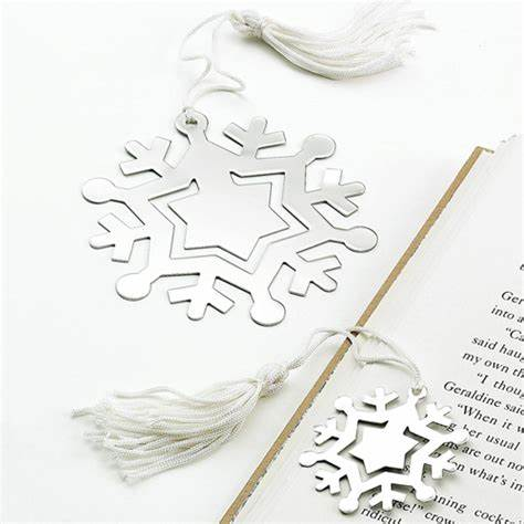 Shiny silver flat snowflake shaped bookmark with a white tassel. The center of the bookmark can be engraved with a special message.