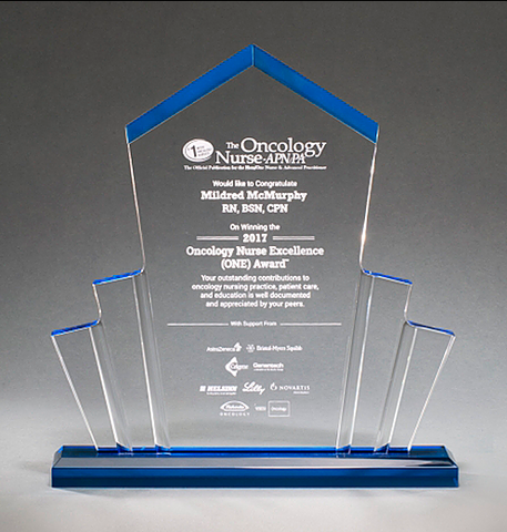Large spotlight shaped acrylic award with a pointed top and a blue base that shines throughout.