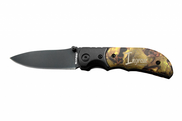 Large tactical camouflage knife featuring a handle with a realtree type design and an engraved name. The top of the knife is black and extends to a black blade.