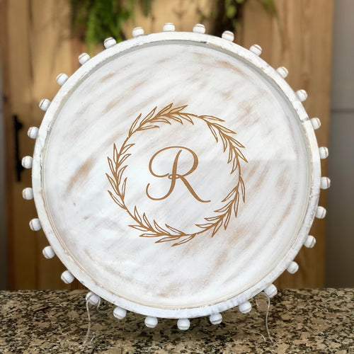 Large round wood white washed tray featuring a beaded edge and engraved with a wreath and an