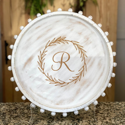 "Large round wood white washed tray featuring a beaded edge and engraved with a wreath and an ""R"" in the center."