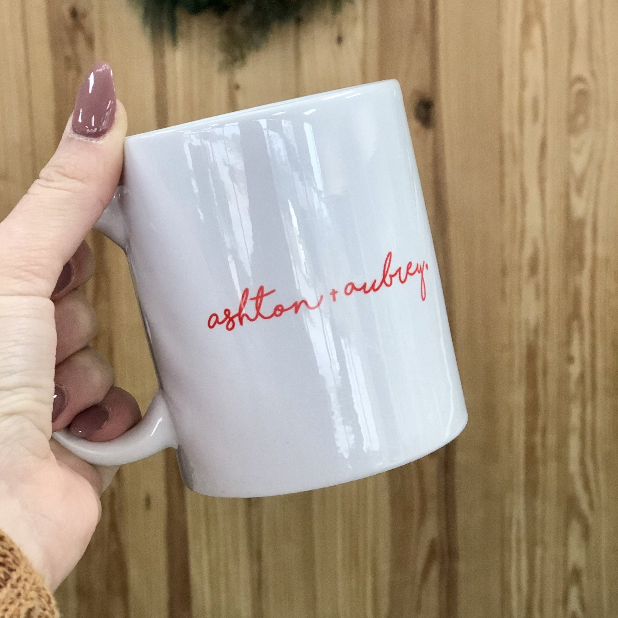 White ceramic coffee mug engraved with two names in a red cursive font.