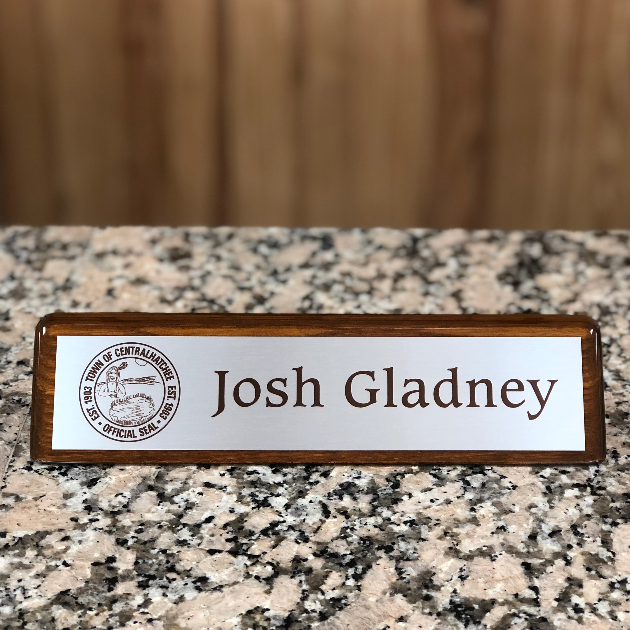 Walnut finish glossy desk bar with a satin silver plate engraved with a logo to the left followed by a name in brown font to match the wood finish.