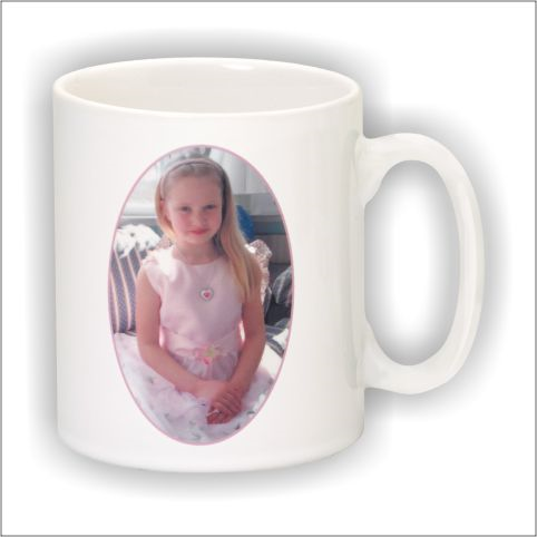 White glass coffee mug engraved an oval shaped photo of a young child.