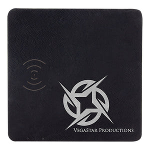 Black leatherette square phone charging mat. The phone charger is engraved with a silver company logo.