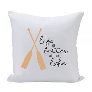 "White square pillow with black letters that reads ""Life is better at the lake"" with two tan paddles crossed to the left."