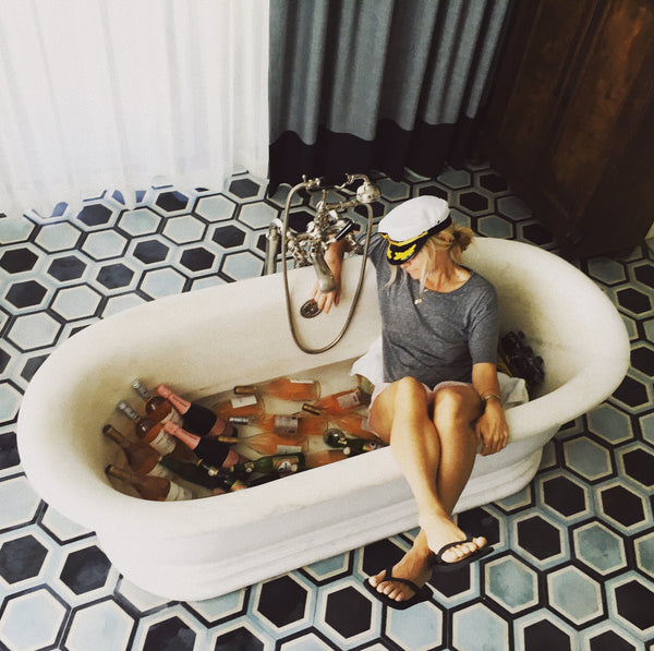 Blond lady in a tub with rose bottles.