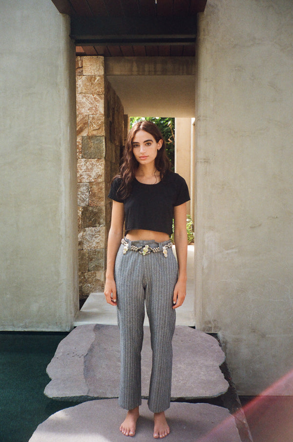 Model wearing cropped black t-shirt and grey pinstripe trousers in Punta Mita, Mexico