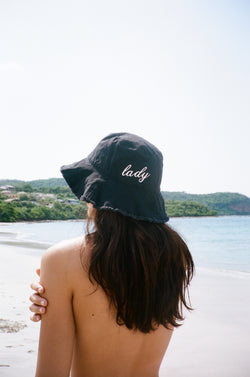 Model on beach in Mexico wearing black embroidered bucket hat.