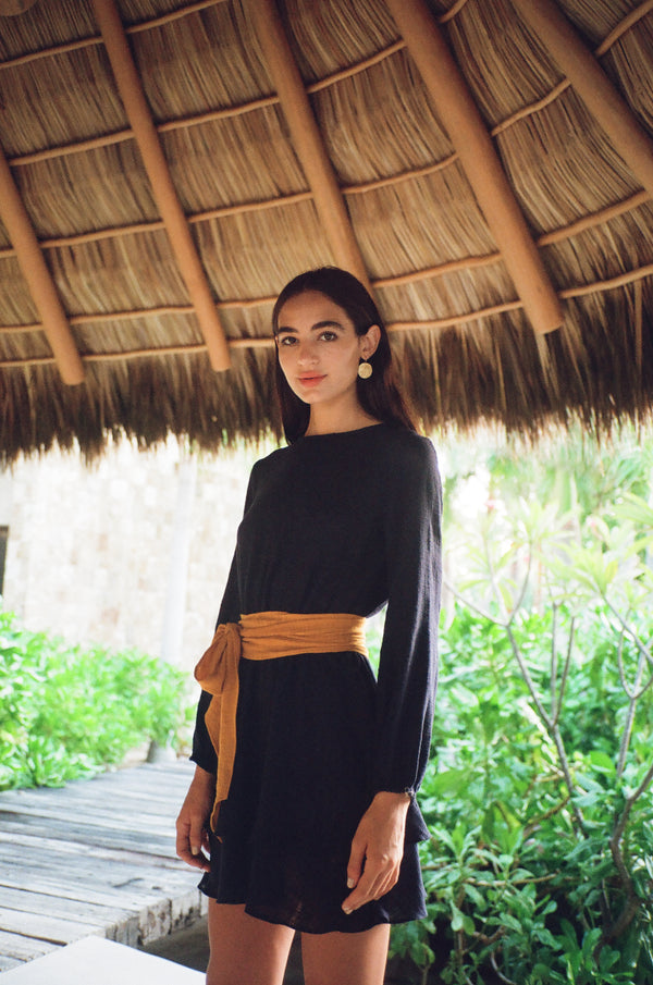 Model wearing long sleeve navy mini dress with gold waist tie in Punta Mita, Mexico.