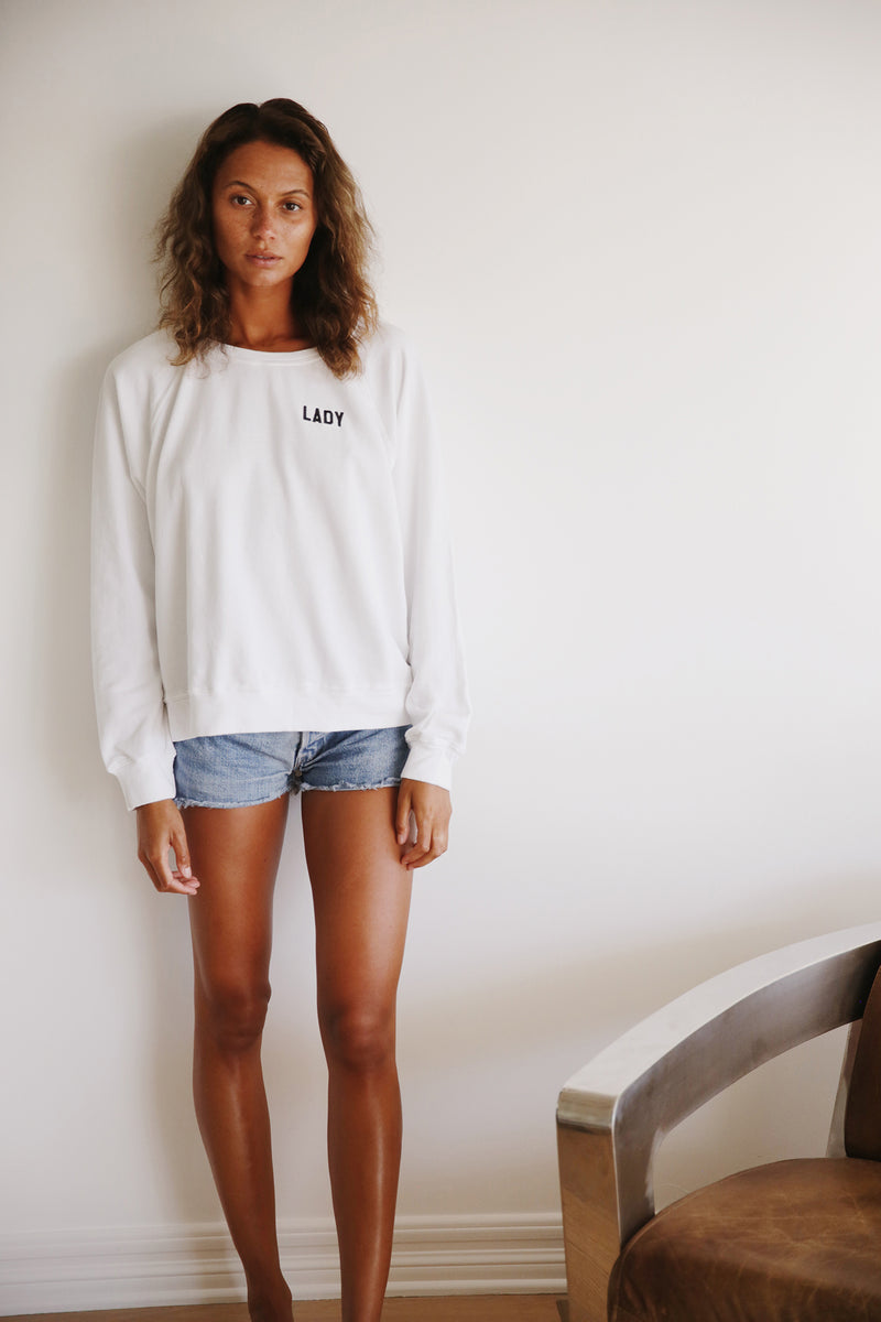 Model wearing the lady & the sailor Brentwood Sweatshirt in Lady White with Black Embroidery.