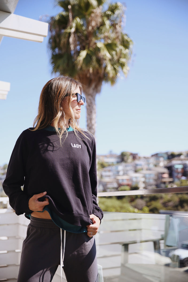 Model wearing the lady & the sailor Brentwood Sweatshirt in Lady Black with White Embroidery.