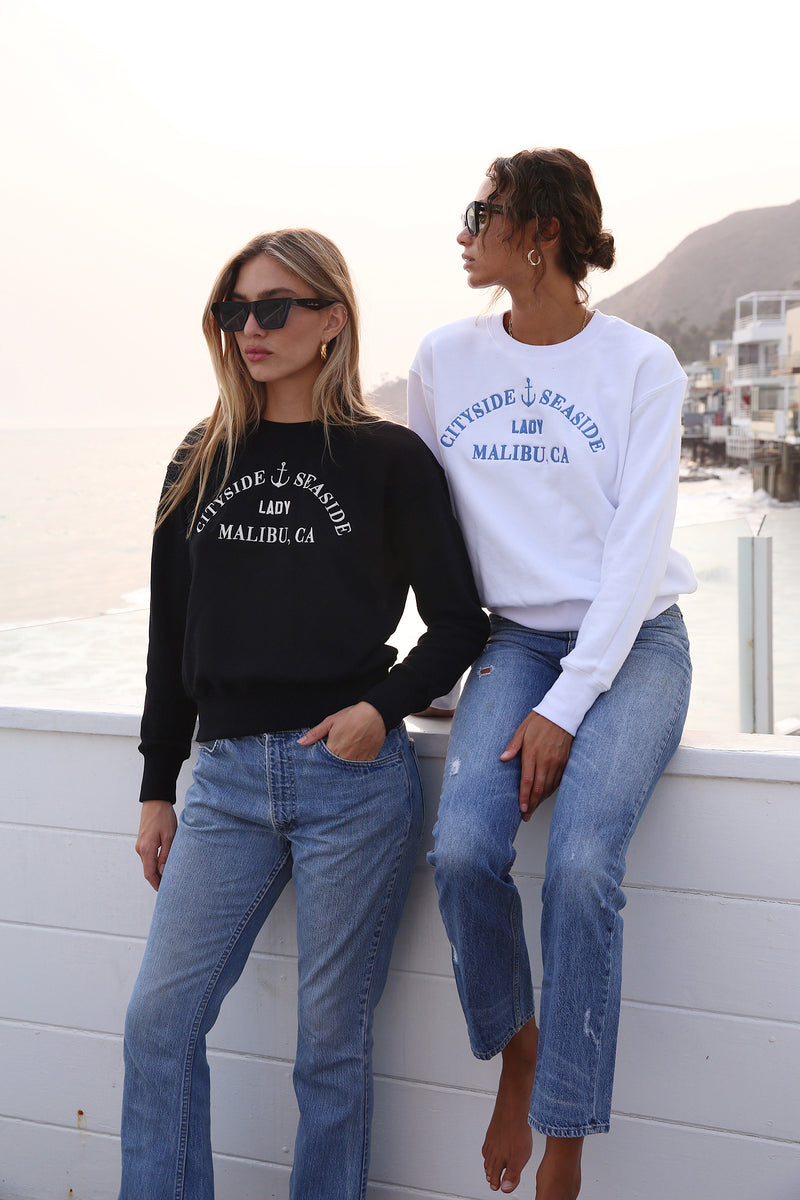 "Model wearing the lady & the sailor Embroidered Varsity Crewneck Sweatshirt in White ""Malibu""."