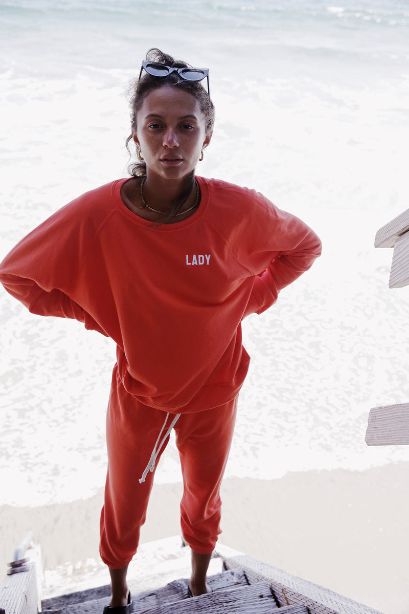 Model wearing the lady & the sailor Brentwood Sweatshirt in Lady Vermillion Orange with White Embroidery.