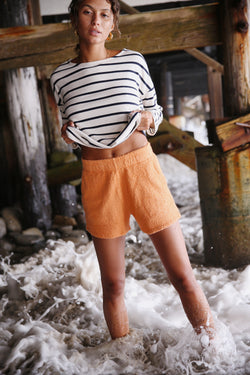 Model wearing the lady & the sailor Weekend Shorts in Tangerine Boucle.