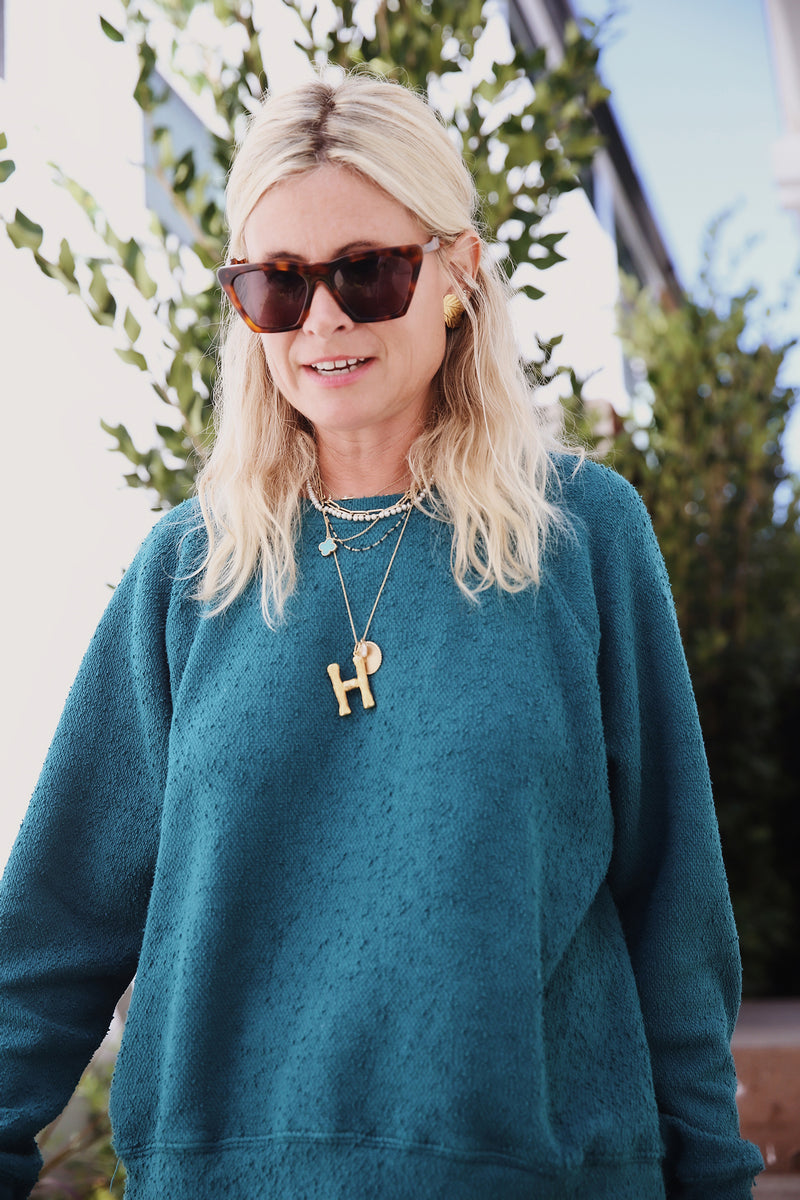 Model wearing the lady & the sailor Brentwood Sweatshirt in Emerald Bay Green Boucle.
