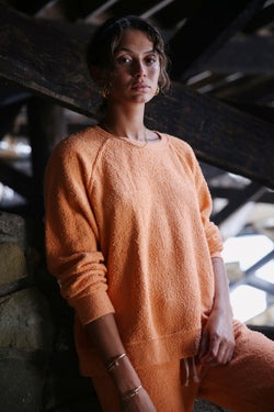 Model wearing the lady & the sailor Brentwood Sweatshirt in Tangerine Boucle.