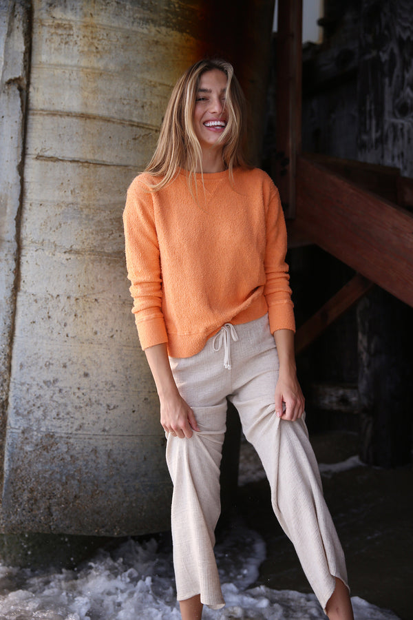 Model wearing the lady & the sailor Varsity Crewneck in Tangerine Boucle.