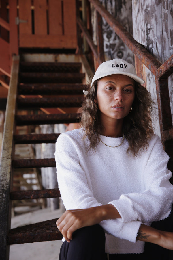 Model wearing the lady & the sailor Vintage Sweatshirt in Vanilla Boucle with Lady Baseball Cap in Ecru.