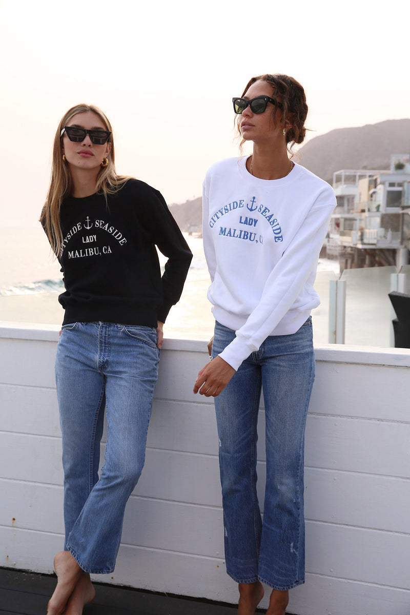 "Model wearing the lady & the sailor Embroidered Varsity Crewneck Sweatshirt in Black ""Malibu""."