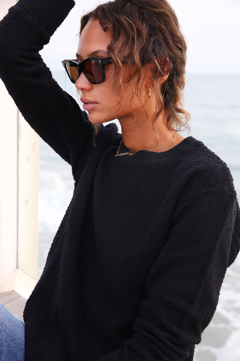 Model wearing the lady & the sailor Embroidered Varsity Crewneck Sweatshirt in Black Boucle.