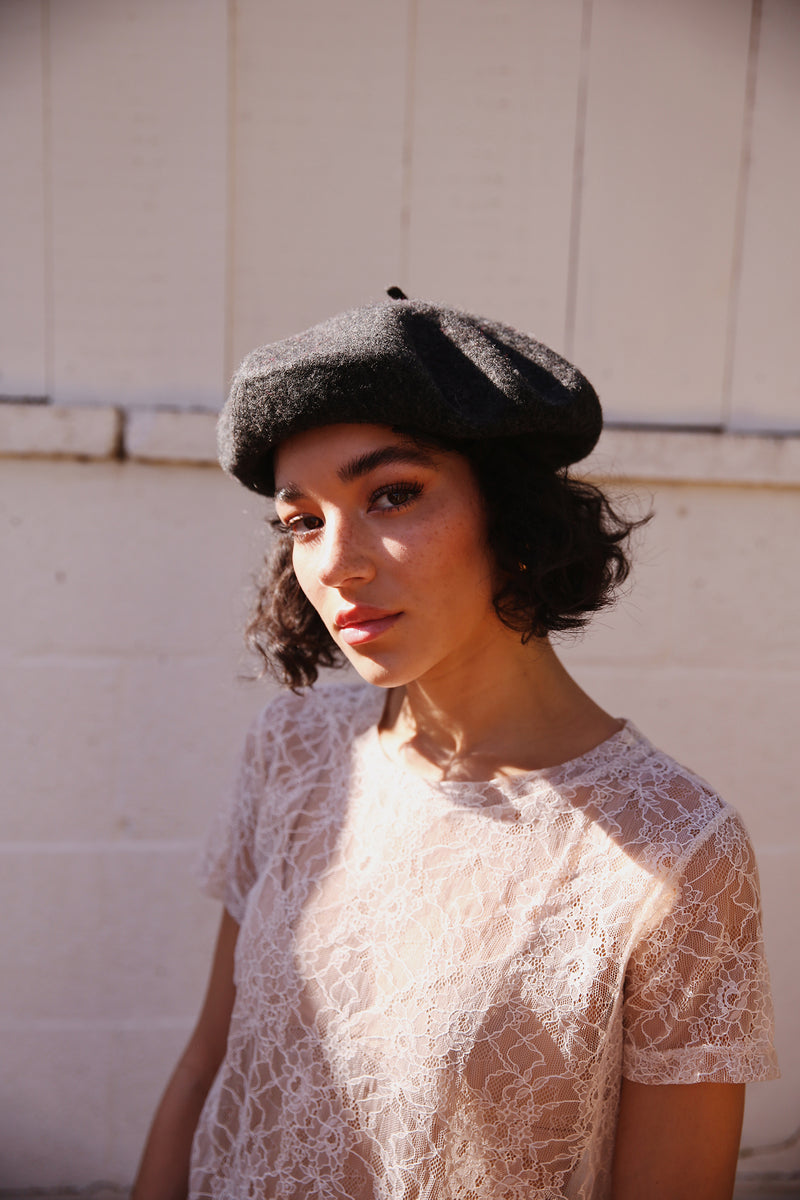 Model wearing Hatattack Wool Beret in Charcoal.