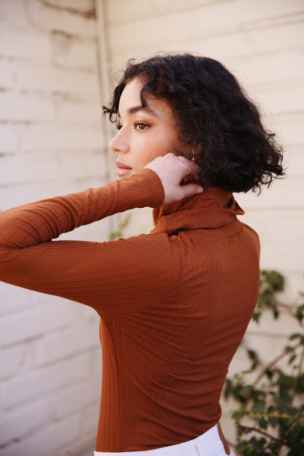 Model wearing the lady & the sailor Classic Turtleneck in Copper Pointelle.