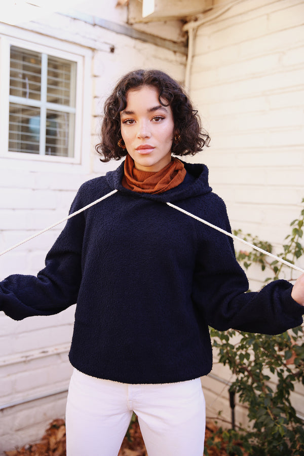 Model wearing the lady & the sailor Tomboy Hoodie in Navy Boucle.