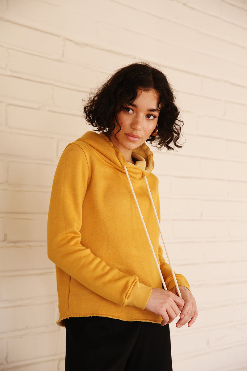 Model wearing the lady & the sailor Raw Bottom Hoodie in Golden Hour Fleece.